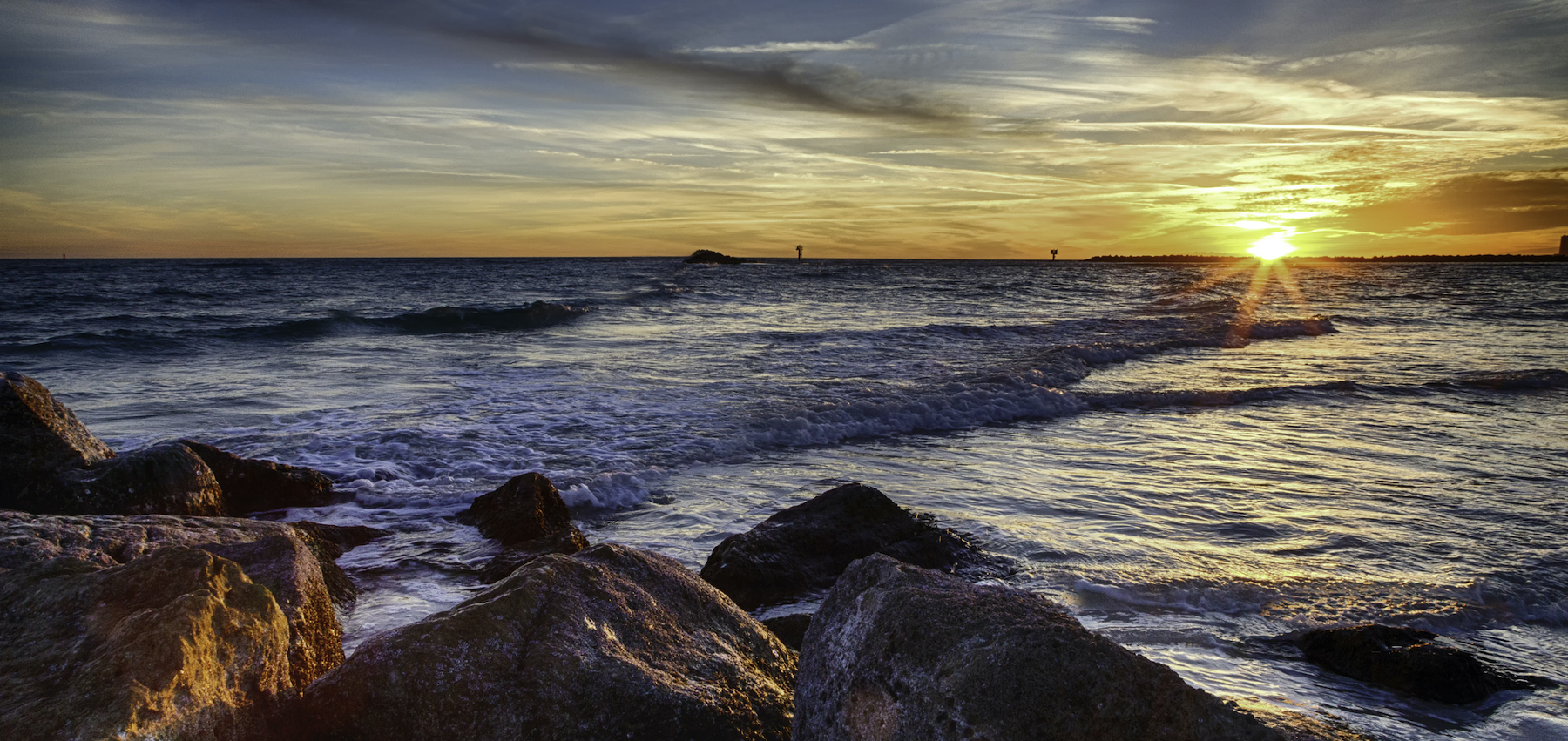 view of the sun setting in orange beach alabama with rocks in the foreground