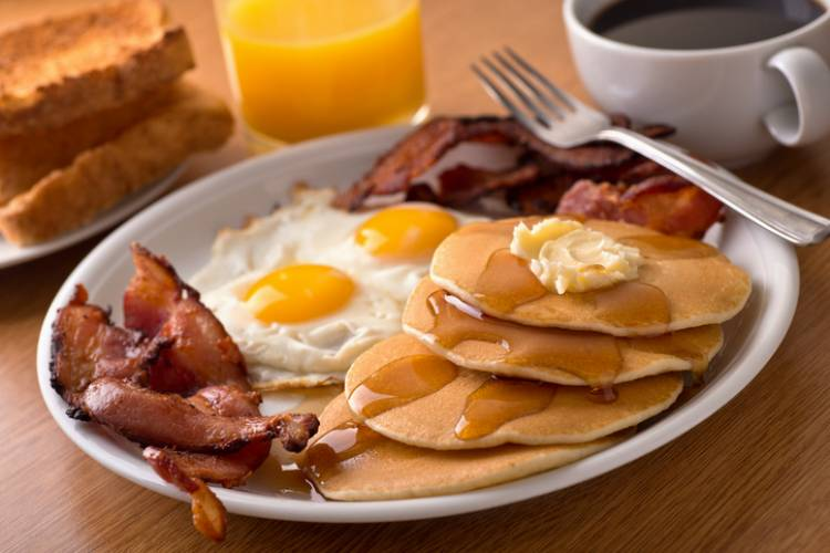 big plate of breakfast food with pancakes, eggs, bacon, and coffee