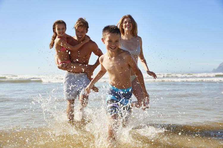 family splashing water at beach