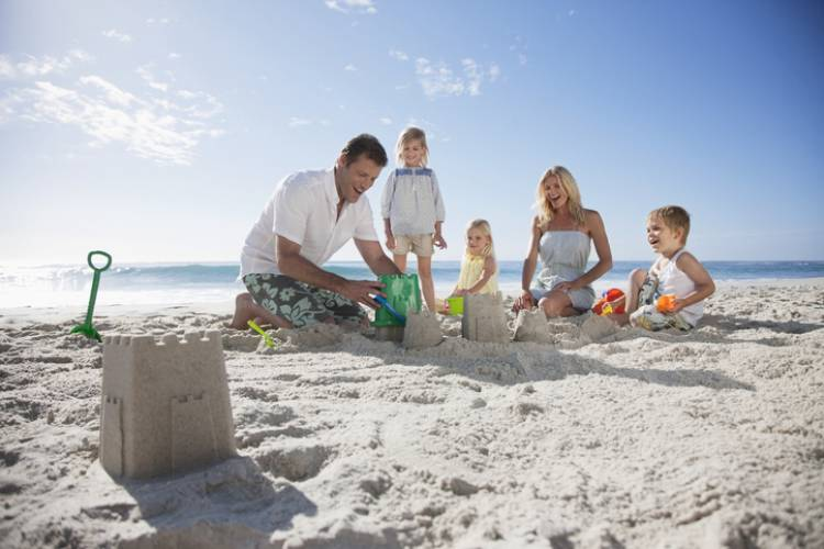 young family at the beach mom and dad and three kids building sandcastles