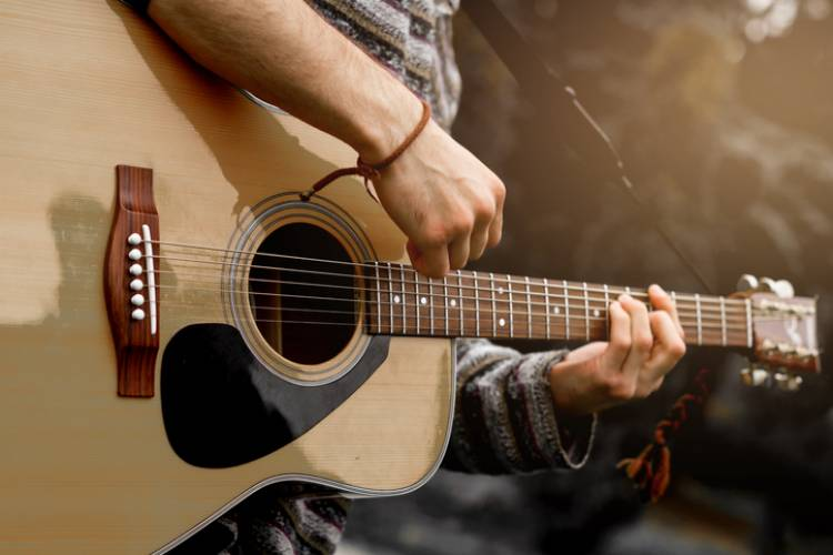 close up acoustic guitar being played by man