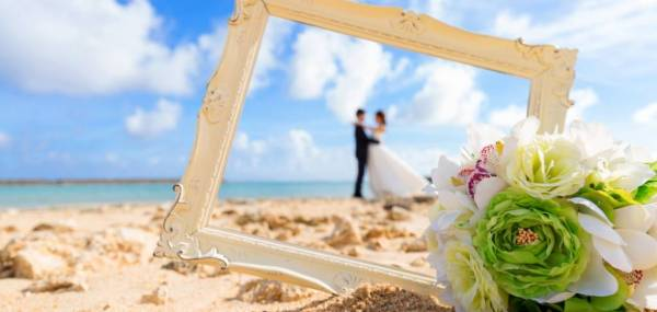 photo frame with married couple in the background and flowers close up on beach