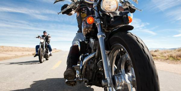 close up of man on motorcyle and another person on a bike in the background on open road