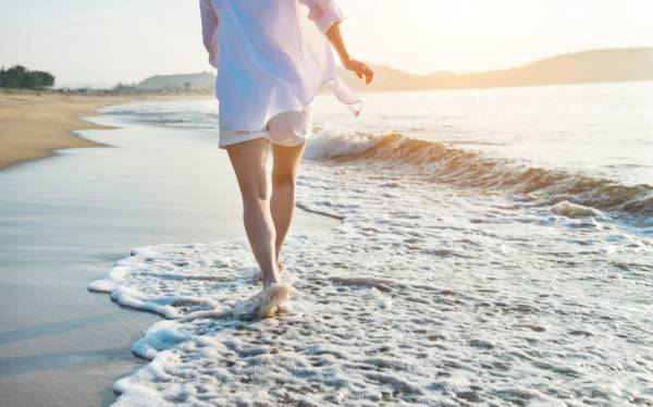 woman dressed in white beach clothes walking on the beach